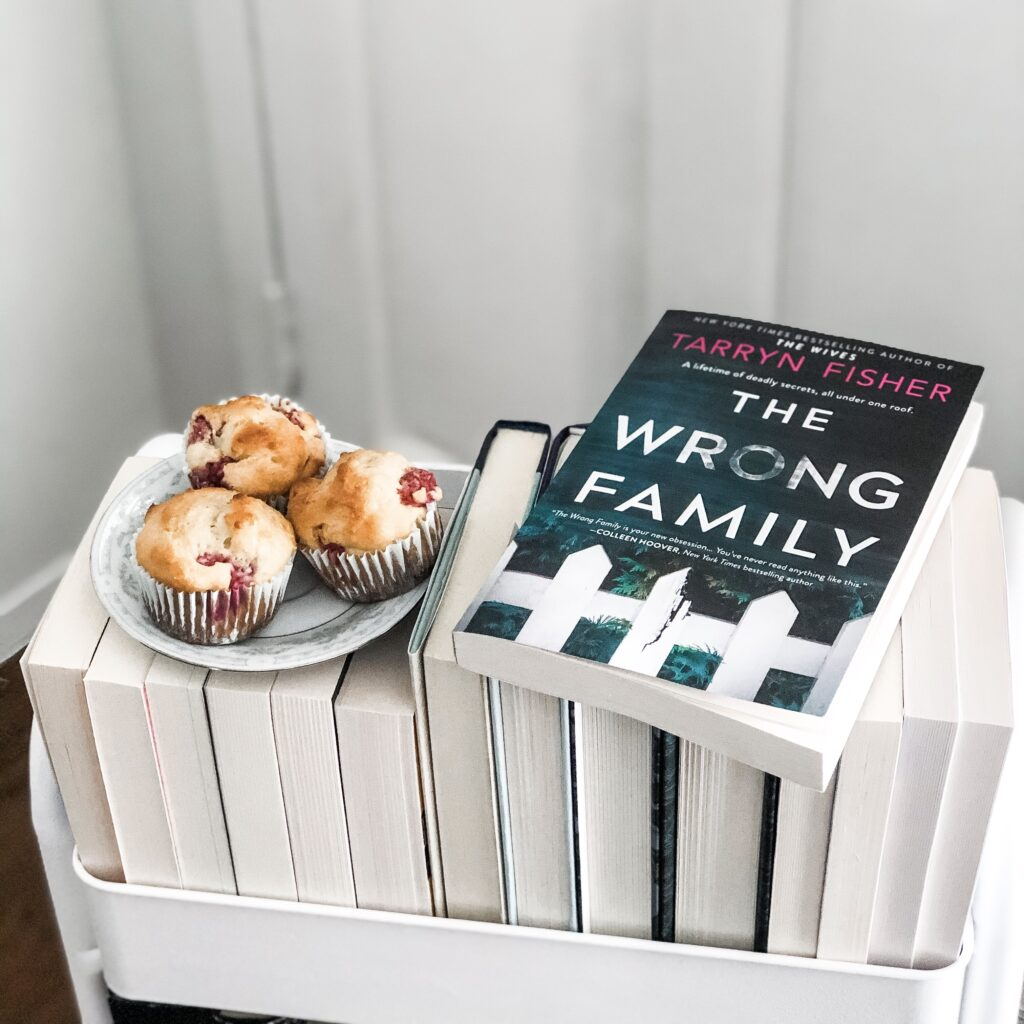 The Wrong Family paperback book on a white book cart with a plate of muffins next to it.