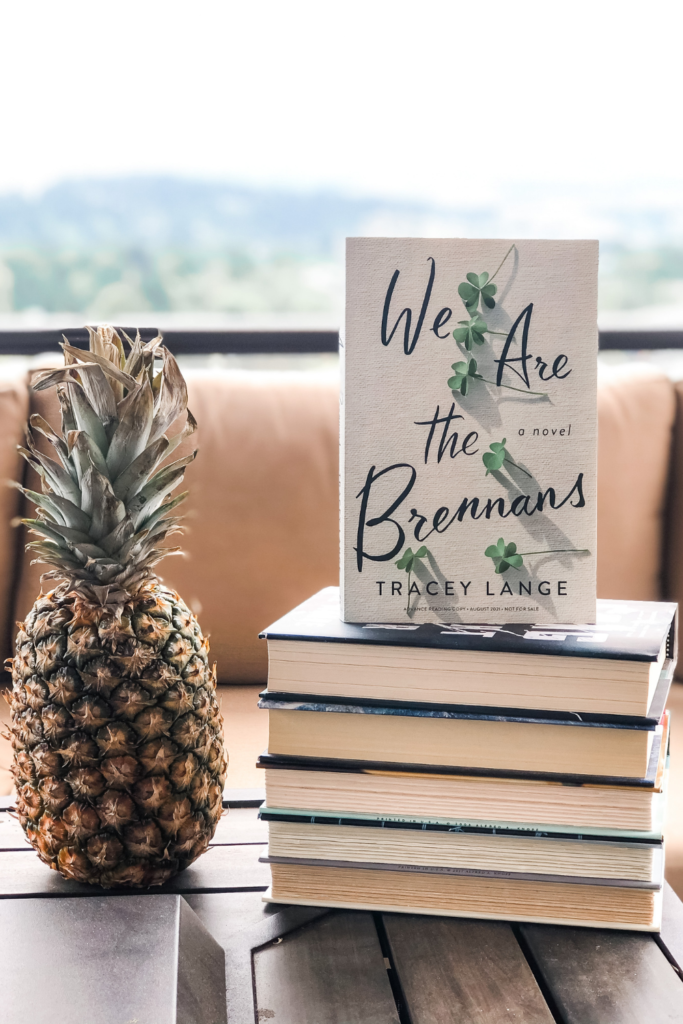 We Are the Brennans paperback book on a stack of books with a pineapple next to it